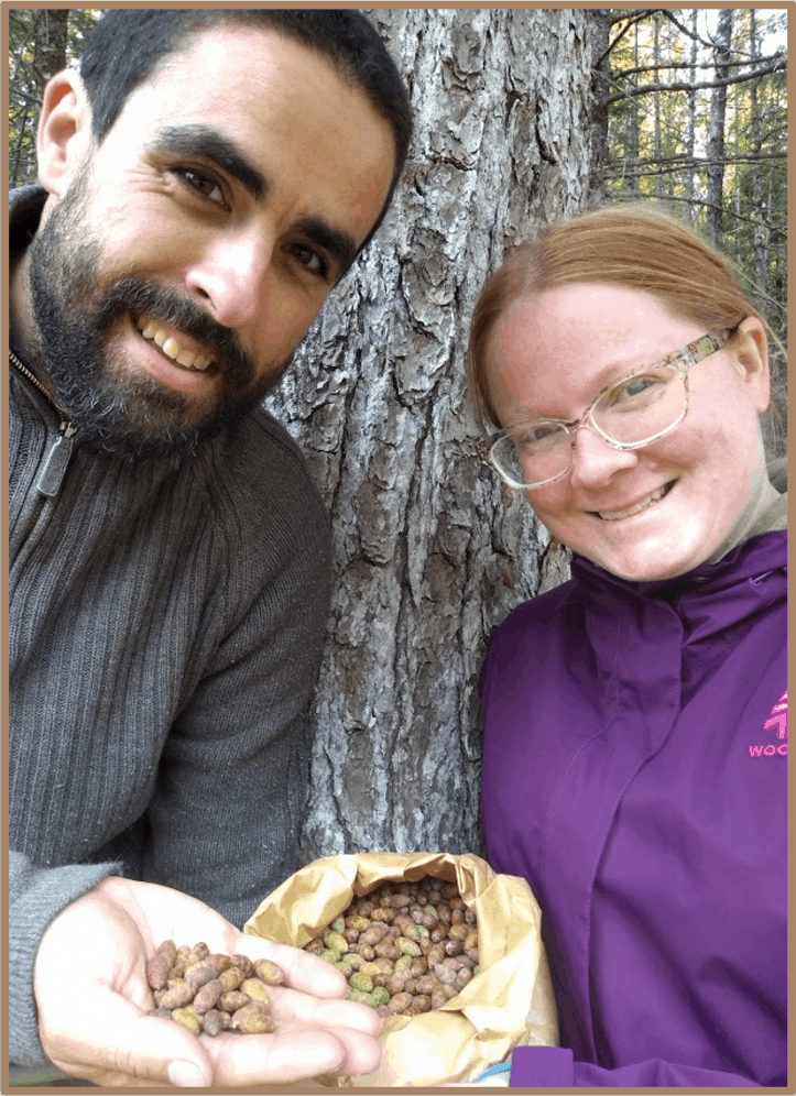 Alain and Sarah holding a bag of hemlock seeds they collected