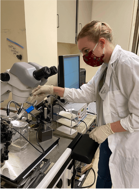 Student Kayla Gaudet working in a laboratory with a large microscope and gas chromatography set up.