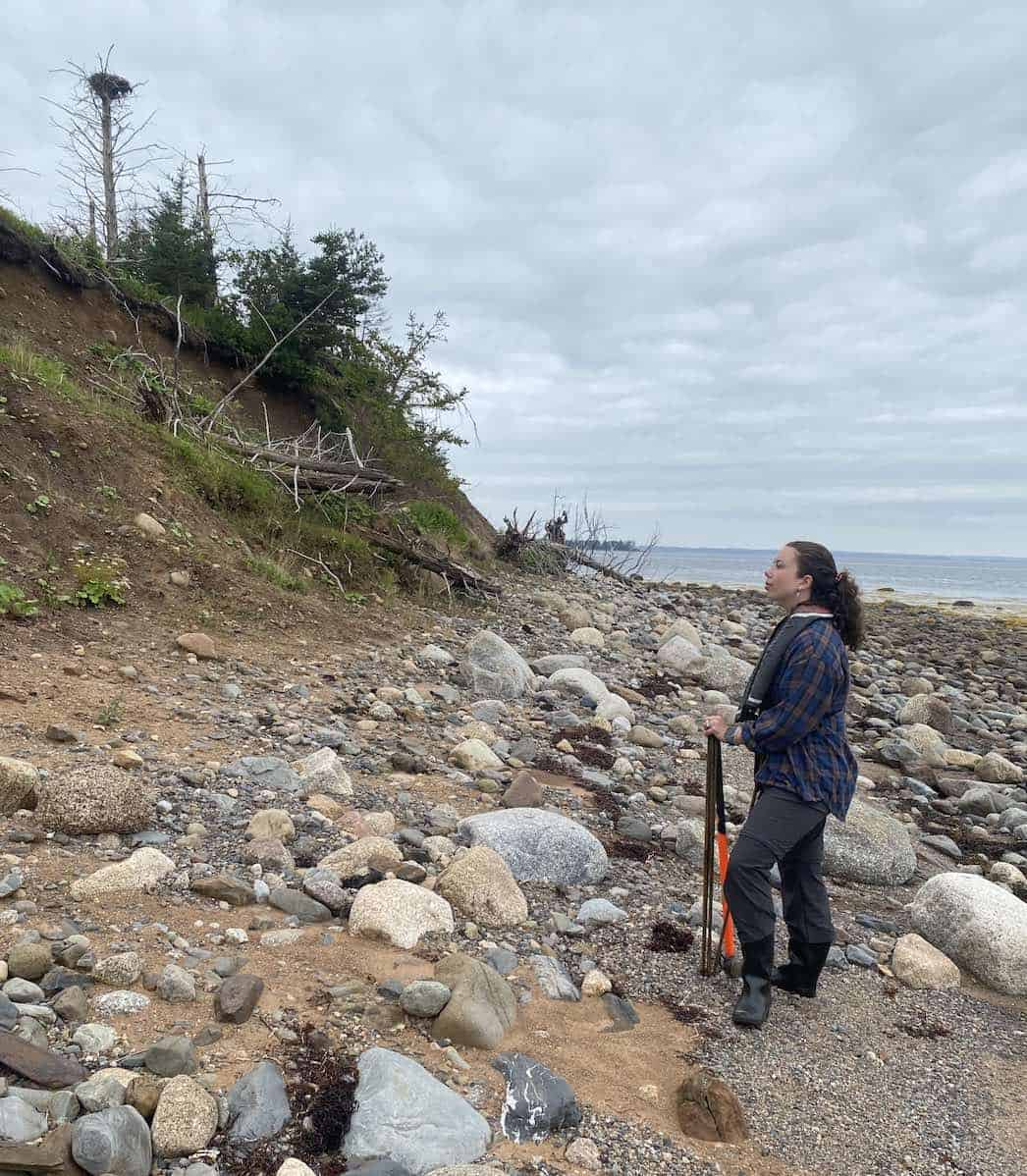 Student Natalie surveying the coast of an island for locations to sample